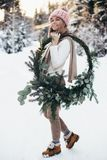 Blonde young lady with christmas wreath in winter forest. Young blonde lady in pink knitted hat hold christmas wreath with snowy winter forest on background stock images