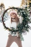 Blonde young lady with christmas wreath in winter forest. Young blonde lady in pink knitted hat hold christmas wreath with snowy winter forest on background royalty free stock photos