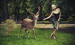 Young blonde lady running with deer Stock Photo