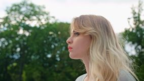 A Young Blonde Lady Turning Back her Head Outdoors. Soft focus. Dolly shoot Stock Photo