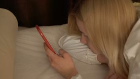 Young blonde lies on couch and uses her phone. Pretty female is messaging with friends and types a message on her touchscreen. Close-up. Camera in motion stock video footage