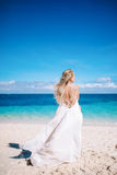Young blonde long hair bride in long white dress with open back standing on the white sand beach. stock photo
