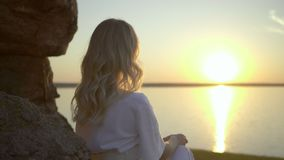 Blonde is sitting on the lake shore. Young blonde with long hair is sitting on the lake shore looking at the sunset stock video
