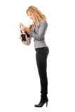 Young blonde looks in her handbag Royalty Free Stock Images
