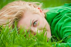 Young blonde lying in a grass Royalty Free Stock Image