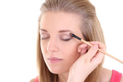 Young blonde with make-up brush over white Stock Image