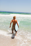 Young blonde man holding his surfboard Stock Images