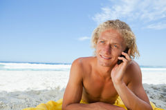 Young blonde man lying on the beach while talking on the phone Stock Images