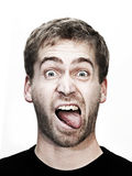 Young blonde man makes grimace. With mouth wide open and tongue outside Royalty Free Stock Images