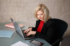 Young blonde manager checking financial results on tablet Stock Photos