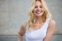Young blonde model with long hair in white tank top stock images