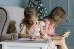 Young blonde mom sitting on couch in pink blouse writing plans. Christmas tree. Daughter raws pictures in the album with stock image