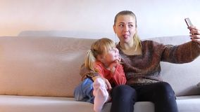 Young mother with daughter sitting on couch and posing on phone for selfie. Young blonde mom sitting with small daughter on couch and posing on phone for selfie stock video