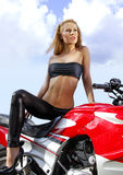 Young blonde on a motorcycle. Pretty blonde woman on a big red motorcycle Royalty Free Stock Photo