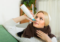 Young blonde with nasal spray Stock Photo