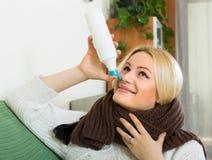 Young blonde with nasal spray Stock Photos