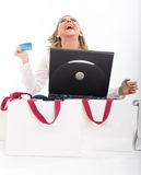 Young blonde in an online shopping spree. Exstatic young blond woman holding a credit card in front of a computer surrounded by shopping bags Stock Image