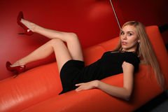 The young blonde on a orange sofa Royalty Free Stock Images