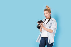 Young blonde photographer is shocked about photo she made. Royalty Free Stock Photos