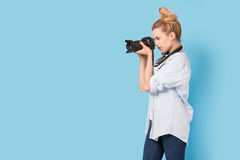 Young blonde photographer is taking a photo. Stock Images
