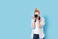 Young blonde photographer is taking a photo. Royalty Free Stock Photos