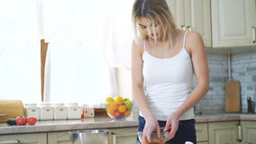 Young blonde pickling meat on the kitchen in 4K stock footage