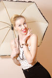 Young blonde pin-up lady under umbrella Stock Photos