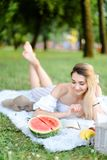 Young pretty woman lying on plaid in park, reading book near watermelon and hat. royalty free stock photography