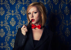 Young blonde with red lips and smoking pipe wearing suite Royalty Free Stock Image