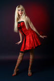 Young blonde in a red satiny dress Royalty Free Stock Images