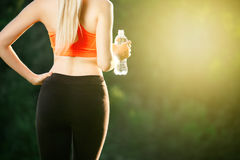 A young blonde in a red top and black pants holds a bottle of water in the hands. Concept of healthy eating and sport Royalty Free Stock Images