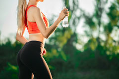 A young blonde in a red top and black pants holds a bottle of water in the hands. Concept of healthy eating and sport Royalty Free Stock Image