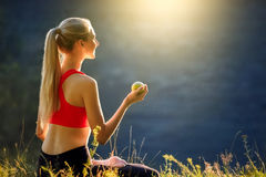 A young blonde in a red top and black pants sits on the grass in nature. A sporty woman holds a green apple in her hands Royalty Free Stock Photo