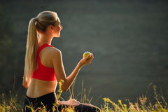 A young blonde in a red top and black pants sits on the grass in nature. A sporty woman holds a green apple in her hands Royalty Free Stock Images