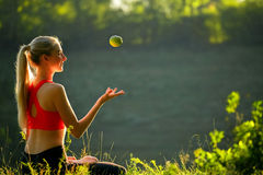 A young blonde in a red top sits on the grass in nature. A sporty woman throws holds a green apple in her hands Royalty Free Stock Photos