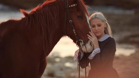Young blonde in retro dress at sunset on the background of the sea taking care of her horse, slow motion stock video footage