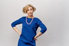 Young blonde with short hair and curls, posing for Studio shooting. She`s wearing a blue dress and vintage beads. stock photography