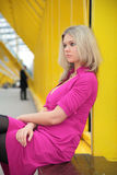 Young blonde sits on footbridge royalty free stock photo