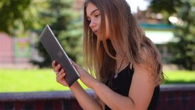 Young blonde sitting on bench working on tablet pc. Female college student using wireless internet in campus park stock footage