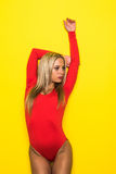 Young blonde slim woman gymnastic dancer in red body  on yellow background Royalty Free Stock Photos