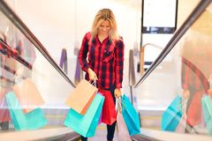 Young woman with shopping bags on escalator in the fashion store. Young blonde smiling attractive woman with long hair with a lot of color shopping bags on Stock Photography