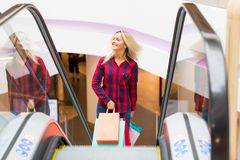 Young woman with shopping bags on escalator in the fashion store. Young blonde smiling attractive woman with long hair with a lot of color shopping bags on Royalty Free Stock Photography