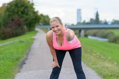 Blonde smiling woman giving thumb up after running. Young blonde smiling woman giving thumb up after jogging near river Stock Image