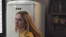 Young blonde standing near refrigerator in flat stock video footage