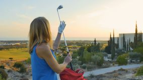 Cheerful young blonde with golf club. Young blonde stands at the golf course near the bag with golf clubs. Pretty woman take the club in her hand and prepares to stock video footage