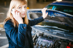 Young blonde stands near car with raised engine compartment hood stock photo