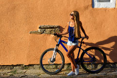 Young blonde stylish woman posing with bike Royalty Free Stock Image