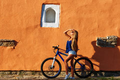 Young blonde stylish woman posing with bike Stock Photos