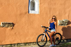 Young blonde stylish woman posing with bike Stock Photography