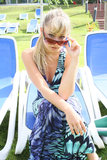 Young blonde with sunglasses on a blue chair Royalty Free Stock Photos